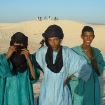 Young men standing in the dunes of Essakane, in the Sahara desert.